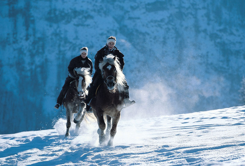 Two people riding horses in crystal mountain